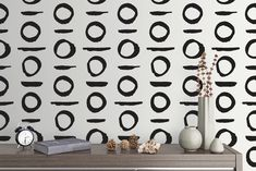 Black circle and line decal pattern on a white wall.