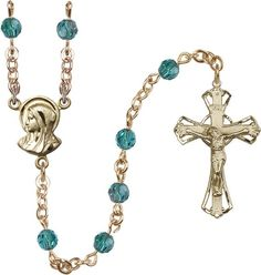 14 Karat Gold Rosary features 5mm Zircon Swarovski beads. The Crucifix measures 1 1/4 x 3/4. The centerpiece features a Madonna medal. Each Rosary is presented