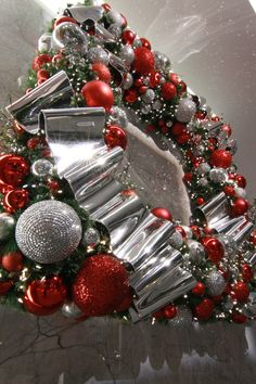 Custom designer Christmas wreath decorated with shiny red and metallic silver ornamentation and ribbon.