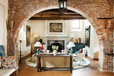 arched brick room divider framing cozy living room with fireplace
