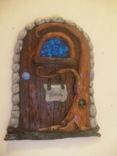 "Fairy door I made from the oven bake clay. I put blue beads in the window and tree trunk. When you bake it the beads melt to make ""glass"". Then I used a little paint to make it look real."
