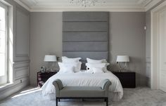 Grey bedroom in a suburban London home with a tall upholstered headboard, carved crown moulding, and light grey carpet