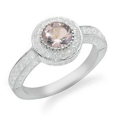 This breathtaking 18k white gold ring features a round shaped bezel set pink amethyst in the middle and sparkling diamonds. The round prong set diamonds have G/H color and VS1/VS2 clarity and surround the pink amethyst and climb down the sides.Different ring sizes may be available. Please inquire for details.