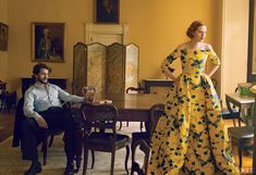 """Behind Closed Doors - Elson and Dancy, as the adulterous wife and cuckolded husband. """"The backdrop of the scene—the whole Pinter play—is loaded,"""" says Dancy, a veteran of the English theater, who now plays an FBI profiler on the TV series Hannibal. Carolina Herrera yellow jacquard ball dress with navy flowers; Saks Fifth Avenue, NYC. On Dancy: Brooks Brothers suit. Salvatore Ferragamo shirt."""