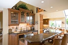 Lamarche - This Kitchen remodel required an open floor plan with modern convenience and we knew just what to do. We began by raising the ceiling to give a more open feel. We then added an island, DeWils Cherry Wood Cabinets, a bar with seating, and remodeled the downstairs guest bathroom. This remodel gave the Lamarches an open kitchen with beautiful natural lighting and a wonderful entertaining area.