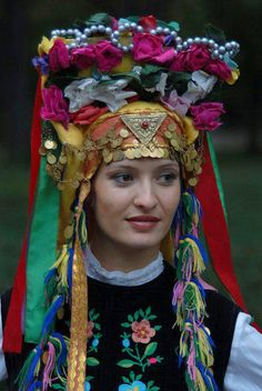Europe | Portrait of a woman wearing a traditional headdress ornamented with flowers and coins, Bulgaria