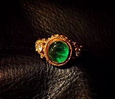 Antique emerald gold ring with diamond studs.
