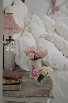 Shabby chic bedroom with lovely pillows and baby pink roses, via shabbychicgirls.blogspot.