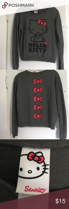 """Sanrio Hello Kitty long sleeve shirt Here sits the adorable and shy """"Hello Kitty"""" with an emphasis on her bright red bow also underneath her is her name with the bright red bow on the """"O"""". Suitable in a dark gray 1/4 length sleeve. BUT a SURPRISE on the back!!! More BIG BRIGHT RED BOWS🎀 down the  LENGHT of your back bone.  One of a kind shirt, never seen this before!!! Tops Tees - Long Sleeve"""