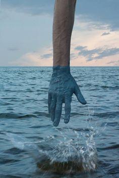 Kevin Corrado trempe sa main dans de la peinture et la place devant des paysages.