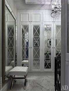 Полы в холле отделаны мрамором Calacatta. Зеркало было привезено из Европы самой хозяйкой квартиры, банкетка выбрана из ассортимента фабрики Eichholtz.