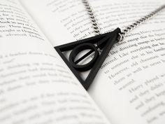 This Deathly Hallows symbol makes a great necklace pendant and enchants any fan of Harry Potter. This is a fully assembled pendant with a rotating center. The top of the pendant features a 2mm hole for threading your favorite necklace or chain. This pendant measures at in: 1.972 w x 1.824 d x 0.197 h. Flick the circle in the center and watch it spin!