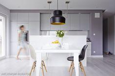 Szara kuchnia kojarzy się z zimnym wystrojem. Oto aranżacja kuchni, która mimo że jest nowoczesna i w kolorze szarym, ma ciepły klimat. Obejrzyj inspirujące zdjęcia kuchni w bloku, która została połączona z salonem i urządzona szarymi meblami.
