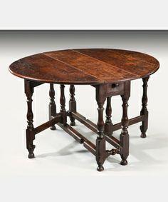 17th Century Jacobean dark oak dining table with gate legs. Rectangular going blocks on legs with ball feet.