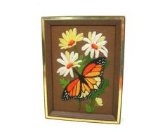 Sweet nature picture for your wall done in yarn embroidery showing yellow and white daisies and a colorful monarch butterfly done on a brown background.  Needlework framed in wood with brass accent trim.  Dated on the back 1979.  Framed size is 8 x6, and the frame is 1-1/2 thick.  Vintage home decor, wall decor.  Excellent, undamaged condition and ready to hang.  Your satisfaction guaranteed or money back if my items are not as described!   *Vintage Item Condition: Items listed have been…