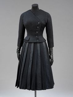 """Suit, Hubert de Givenchy, Paris, France: 1955, wool with moiré silk panels in the skirt. """"This ensemble was designed by the Parisian couturier Hubert de Givenchy (b. 1927) for Leslie Caron (b. 1931), the French film actress and dancer. It was made for a play called 'Orvet' by Jean Renoir, who was Caron's great friend and mentor. He wrote it for her, and also directed it. It was first performed at the Theatre de la Renaissance, Paris, on 12 March 1955."""""""