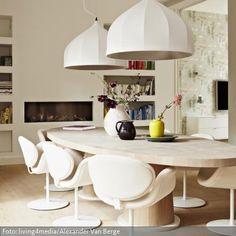 Die Retro-Leuchten über dem ovalen Holztisch aus Massivholz setzen ein Statement. In diesem Esszimmer ist an großen und in ihrer Form groben Möbeln nicht gespart…