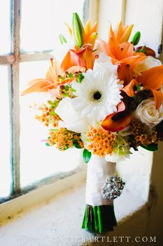 Fall wedding flowers orange and ivory...with antique brooch.