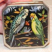 """This is a fabulous Gwenda powder compact - dating c. 1930, it is in amazing vintage condition.  Measuring c. 1.3/4"""" inch square with shaped corners, the gorgeous, vibrant colours of the foil picture depicting two budgerigar birds is set beneath a clear celluloid cover.  Chrome based, all clasps and hinges are in excellent order, and no signs of corrosion, opening to reveal a high polish steel mirror to the top, with an inner opening lid which is fully engine turned, a nice clear powder well…"""