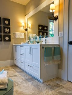 Travertine-style porcelain tile and clean white surfaces define this spa-like master bath, where an antique-style dresser and botanical artwork offer an intriguing focal point.