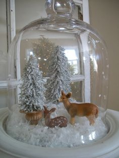 """Dollar store trees and more toys borrowed from the little one are hanging out under the cloche. I scraped off a handfull of styrofoam to create staticy snow for under the glass to give it a """"snow globe"""" effect. I found the styrofoam idea on pinterest here. Sixty-Fifth Avenue: Christmas 2011"""