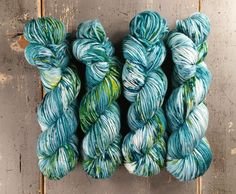 Hand dyed worsted weight yarn. This yarn is dyed in a semi solid teal with a hint of blue and some lighter to white areas. It is speckled with more rich teal green, a few specks of dark blue, and some yellow/green. This listing is for 1 skein of Super Squishy Worsted. This yarn is a