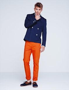 Wear a navy double breasted blazer with orange chinos to create a smart casual look. Navy canvas boat shoes will give your look an on-trend feel.  Shop this look for $121:  http://lookastic.com/men/looks/navy-double-breasted-blazer-and-white-longsleeve-shirt-and-orange-chinos-and-navy-boat-shoes/3878  — Navy Double Breasted Blazer  — White Longsleeve Shirt  — Orange Chinos  — Navy Canvas Boat Shoes