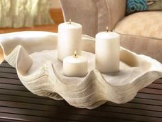 "Simple coastal centrepiece. Fill a large ""faux"" clam shell with sand, add pillar candles & relax & enjoy."