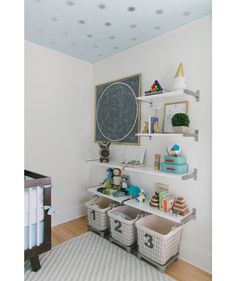 A patterned ceiling elevates this beautifully serene nursery. You can get the look using wallpaper or try a less pricey paint-and-contact-paper DIY. Sleek metal shelving offers a boutique-like storage setup. The deep baskets at the bottom are ideal for stuffed animals and baby blankets (or can function as hampers for a bigger kid).