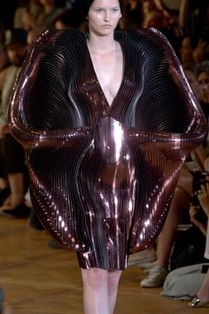 Iris Van Herpen:  The deep maroon fabrication layered in strips to undulate around the body and really obscure the body is dangerously beautiful. Obstructs the body in its natural movement of the arms and legs.