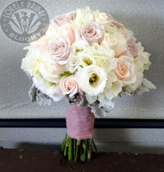 bouquet of roses in ivory, antique and pink champagne with white lisianthus and freesia, created by lovely bridal blooms