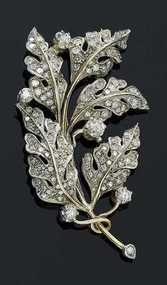 SILVER, GOLD AND DIAMOND BROOCH, ca. 1890. Designed as an oak branch, the leaves set with 143 old-mine-cut diamonds totalling ca. 2.00 ct. French import mark.