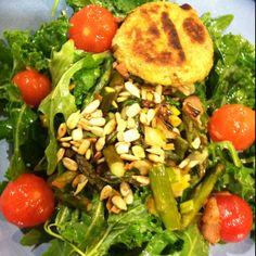 "Kale/arugula salad w blanched tomatoes, roasted asparagus, leeks, sunflower seeds, bacon bits and polenta ""cake"" on the side."