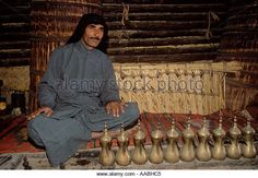 """Marsh Arabs"" man in reed house with a line of coffee pots Iraq. 1984 Southern Iraq Near Basra."
