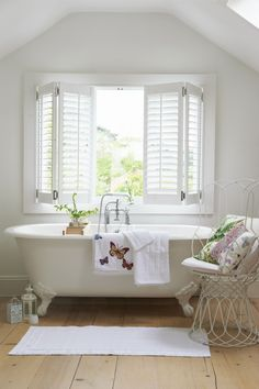 bathtub beneath a large window allows lots of light into the room