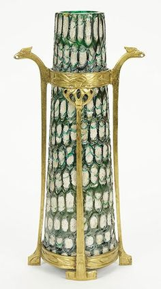 Koloman Moser (Austrian, 1868-1918) A Loetz Vase. Iridescent blackish blue and emerald green honeycomb like trailings on basic geometric tapered slberflitter glass. Bronze Jugendstil mounting with four upright supports and two griffin head handles. Leopold Bauer and Koloman Moser designed this Loetz vase for Baklowitz Height: 12.5""