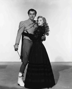 Full publicity shot of Stewart Granger as Andre Moreau holding fencing sword/foil and embracing Eleanor Parker as Lenore.