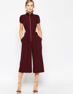 Blonde in a short sleeve maroon zip-up jumsuit with side cutouts
