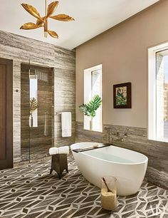 Travertine wall panels and a geometric stone-tile floor lend warm tones to the Dufner Heighes–designed master bath in this Manhattan penthouse. The vintage light fixture is by Angelo Lelli, the framed collage is by Mark Welsh, the tub is by Wetstyle, and the tub fittings are by Ballista | archdigest.com