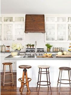 Concrete countertops add a touch of modern chic to this warm and whimsical white kitchen design. Wood vent hood, subway backsplash tiles, glass-front cabinets, assorted old stools around kitchen island. Farmhouse Kitchen Decor, Home Kitchens, Rustic Kitchen, Kitchen Remodel, Kitchen Design, Kitchen Countertops, Rustic Farmhouse Kitchen, Farmhouse Bar Stools, Kitchen Styling