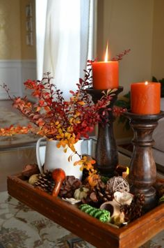"""I love this beautiful fall centerpiece that utilizes items many of us may already have around our home:  candles, wood tray, chunky candle holders, a pitcher and dried floral items.  Just be sure to mix in fall colors and add a little contrast (like the """"white"""" pitcher) to make this arrangement pop."""