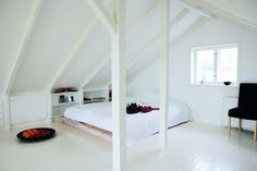 Under the roof. Paint both walls, ceiling and floor in white to make it seem bigger.
