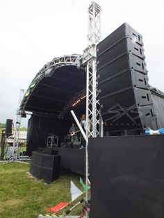 Outdoor stage structure with line array speaker tower. www.sxsevents.co.uk