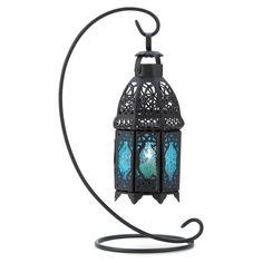 Candle light glimmers through lacy designs turned into sapphire rays of light. This graceful hanging tabletop lantern enchants your home with the magic of a desert night! Weight 2 lbs. Iron and glass.