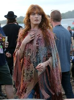 One day after her headlining performance (where she stripped down to her bra), Florence Welch covers up with a colorful poncho to enjoy the festival.   - HarpersBAZAAR.com