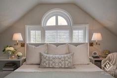 White and grey bedroom features a gray headboard, placed in front of plantation shutter windows, on bed dressed in white and gray bedding and a gray embroidered lumbar pillow flanked by white lacquer open nightstands illuminated by antique brass sconces with white pleated shades.