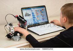 Minsk, Belarus - March 11, 2017: Boy teenager behind the desk programs Lego robot on the Sony laptop in Scratch program. E-learning. Stem education. Modern education for genius kid.