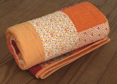 Bright lap quilt for your home. Colors include orange, red and gold.