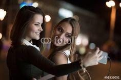 """Laden Sie das lizenzfreie Foto """"Girlfriends taking self picture with smartphoneat night city"""" von antgor zum günstigen Preis auf Fotolia.com herunter. Stöbern Sie in unserer Bilddatenbank und finden Sie schnell das perfekte Stockfoto für Ihr Marketing-Projekt!"""
