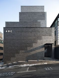 The semi-transparent facade of the ABC Building in Seoul reveals the position of the staircase — fronted by solid brickwork — behind it. Architecture Design, Facade Design, Contemporary Architecture, Landscape Architecture, Exterior Design, Building Architecture, Installation Architecture, Contemporary Houses, Architecture Wallpaper